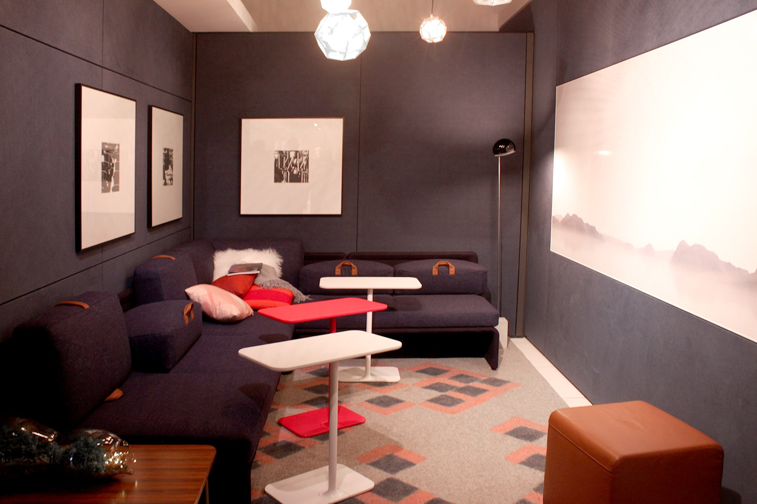 Dark, contemporary lounge seating with pops of reds and pinks.